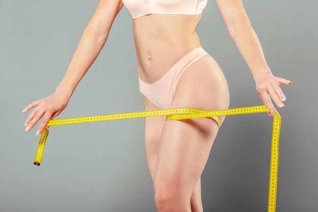 Здоровое женское тело с рулеткой Premium Фотографии
