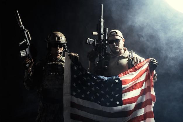 Солдат держит пулемет с национальным флагом Premium Фотографии