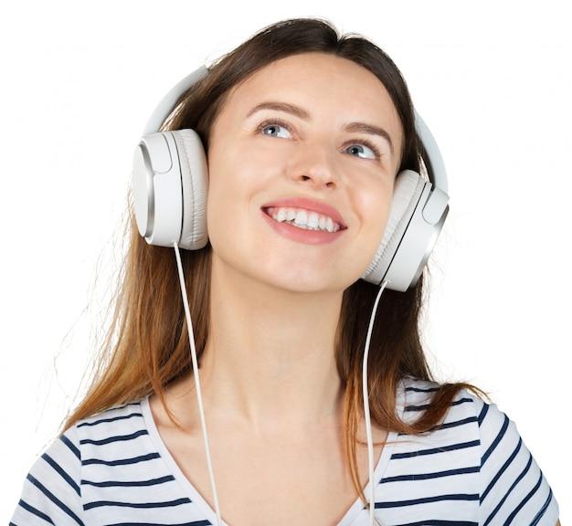 白で隔離される白いヘッドフォンで音楽を聴く若い幸せな女 Premium写真