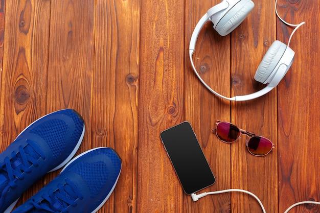 Кроссовки и мобильный телефон с наушниками на деревянный стол Premium Фотографии