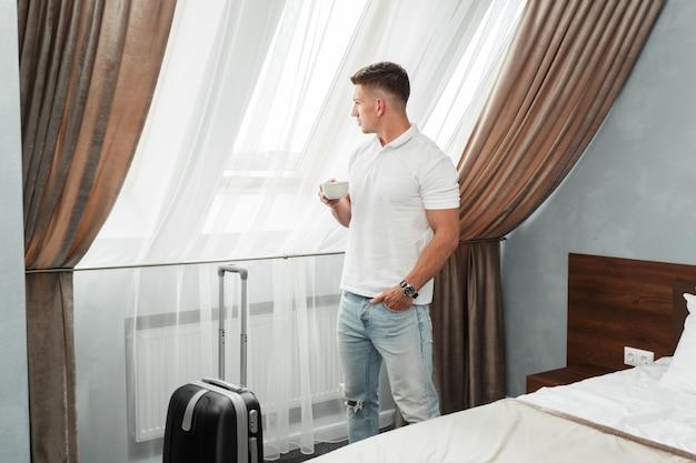 若い男のビジネス旅行者のホテルの部屋の宿泊施設 Premium写真