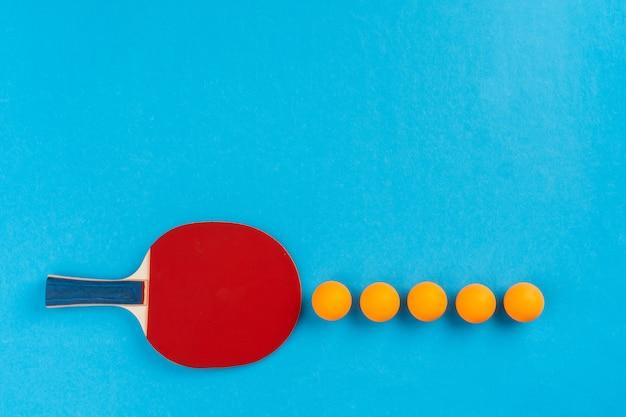 卓球ラケットと青の背景にボール Premium写真