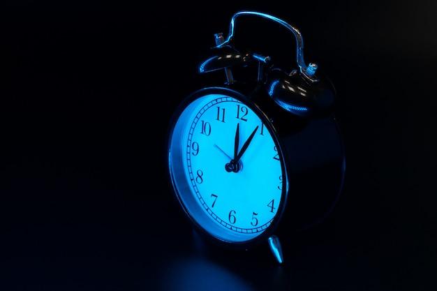 目覚まし時計は黒の背景にクローズアップ Premium写真