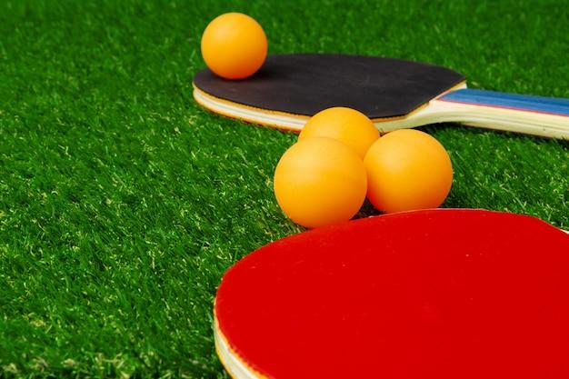 草の上のピンポンラケットとボール Premium写真