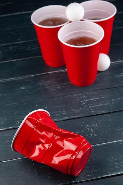赤いカップとビールピンポンのボールと木製のテーブル Premium写真