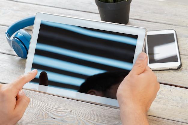Руки человека, держащего планшетный компьютер над деревянным столом рабочей области Premium Фотографии