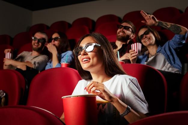 映画館で映画を見ている友人と若い女性 Premium写真