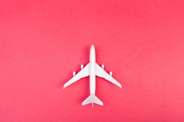 モデル飛行機、パステルカラーの背景上の飛行機。フラットレイアウトデザイン。 Premium写真
