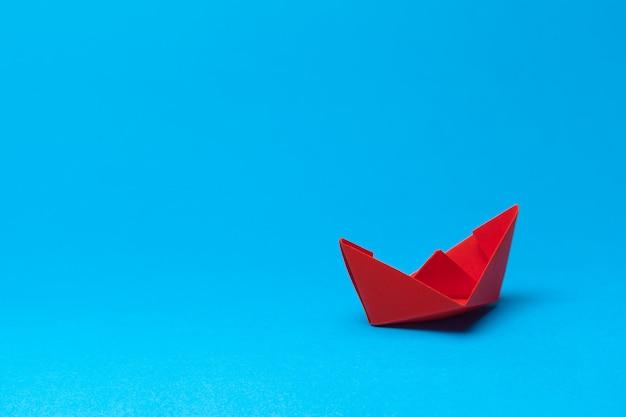 Оригами бумажный кораблик на синем фоне Premium Фотографии