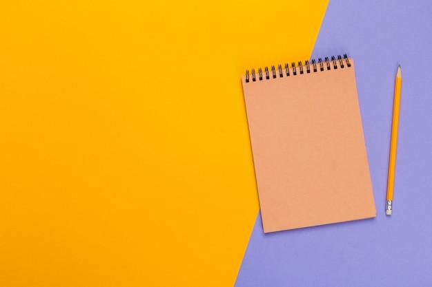 あなたのデザイン、トップビューの明るい二色背景に空白の紙メモ帳 Premium写真