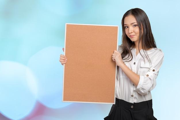 Улыбается случайный женщина, держащая пустой пробковой доске Premium Фотографии