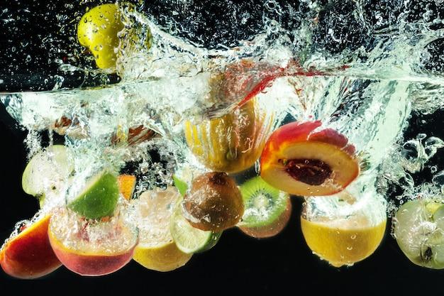 多くの果物が水にはねかける Premium写真