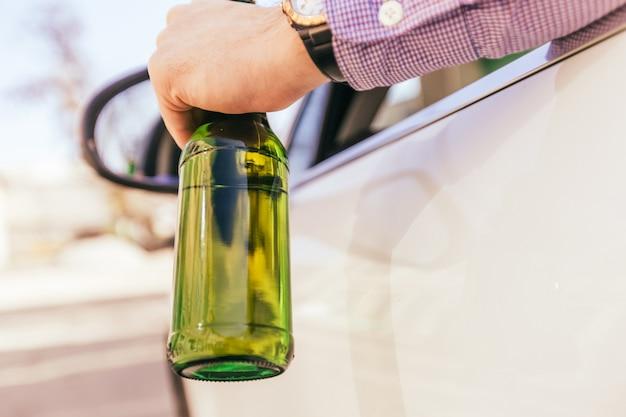 車を運転中にアルコールを飲む男性 Premium写真