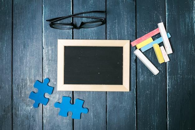 Маленькая доска, кусочки головоломки, очки и цветные мелки Premium Фотографии