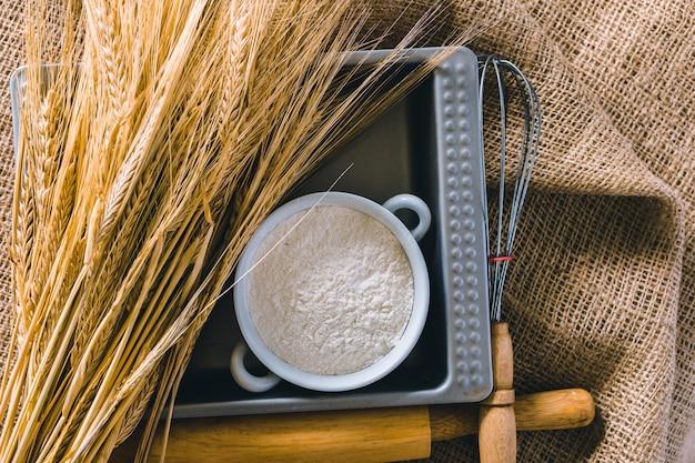 Пшеница и кухонные инструменты на вретище Premium Фотографии