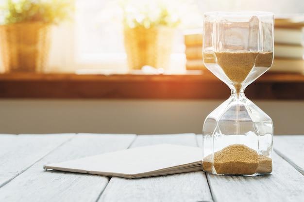 木製の机の上のカレンダーと砂時計 Premium写真
