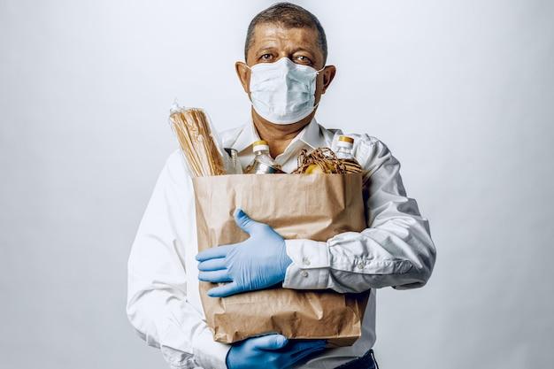 食料品店からの袋で防護マスクの男 Premium写真
