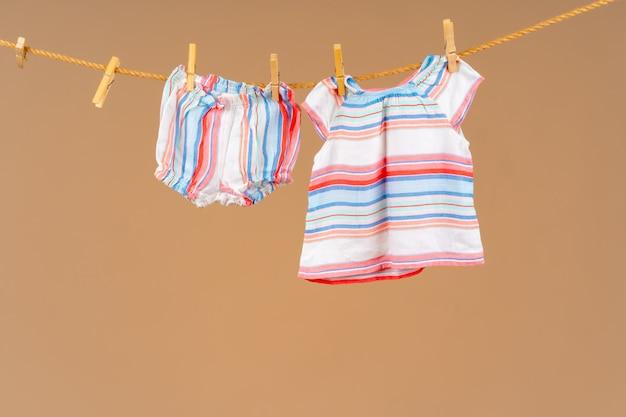 乾燥するために洗濯物に固定された子供のアパレル Premium写真