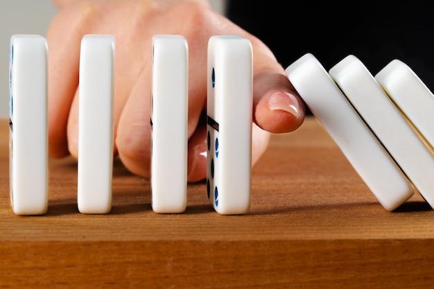 女性の手がドミノを転倒 Premium写真