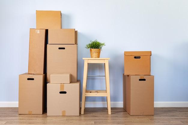 Движущиеся ящики с упакованным материалом и стулом для переезда Premium Фотографии