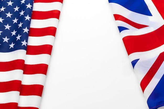 アメリカの旗と一緒に手を振っているブリティッシュユニオンジャックの旗 Premium写真
