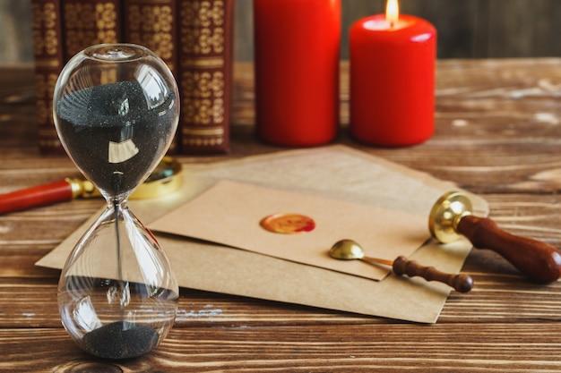 ヴィンテージの砂時計とグランドシール付きの古い手紙の木製デスク Premium写真