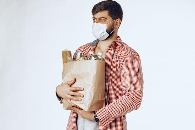 Человек в защитной медицинской маске с сумкой из продуктового магазина. доставка еды Premium Фотографии