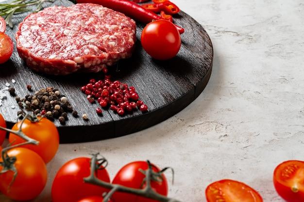 テーブルの上のスパイスとトマトの新鮮な生の自家製カツレツ Premium写真