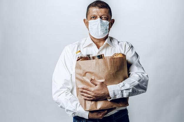 Человек в защитной медицинской маске с сумкой из продуктового магазина Premium Фотографии