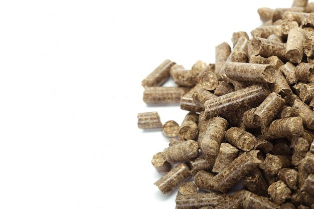 Стек из деревянных гранул для био энергии, на белом фоне, изолированные Premium Фотографии