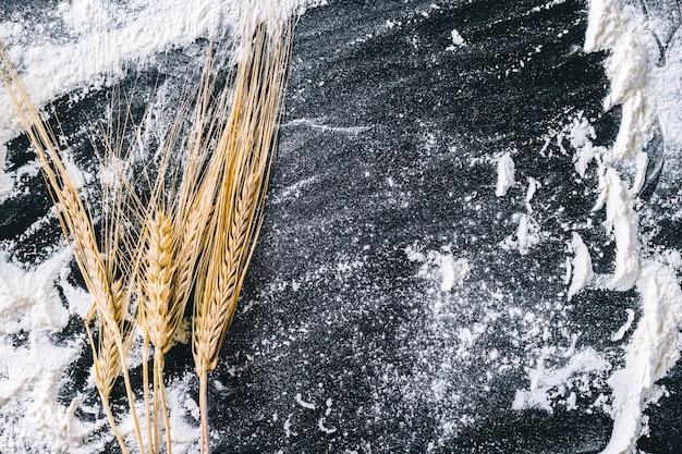 Колосья пшеницы и мука на черном Premium Фотографии