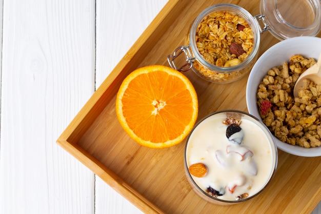 Вкусный завтрак с мюсли, йогуртом и фруктами в стеклянной миске Premium Фотографии