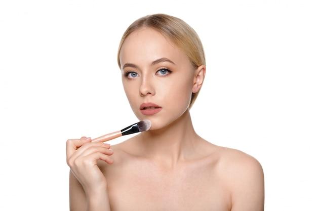 メイクアップブラシでポーズ笑顔の美しい半分裸の女性の美しさの肖像画 Premium写真