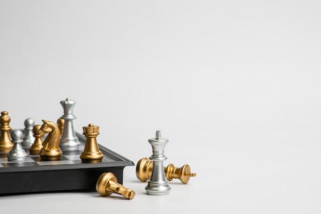 Концепция руководства шахмат при шахматы золота и серебра изолированные в белой предпосылке. Premium Фотографии