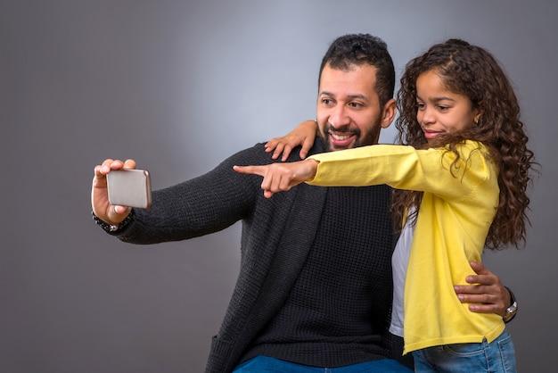 黒人の父親が娘と一緒にセルフィーを撮る Premium写真