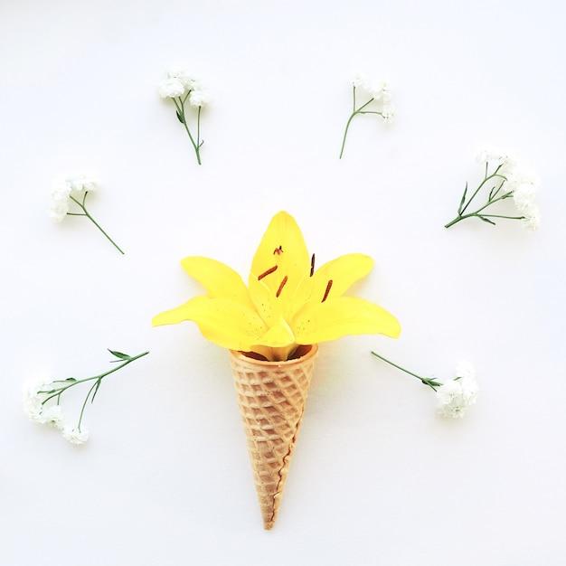白い背景の周りのアイスクリームと白い花カスミソウの黄色いユリの角を花します。 Premium写真