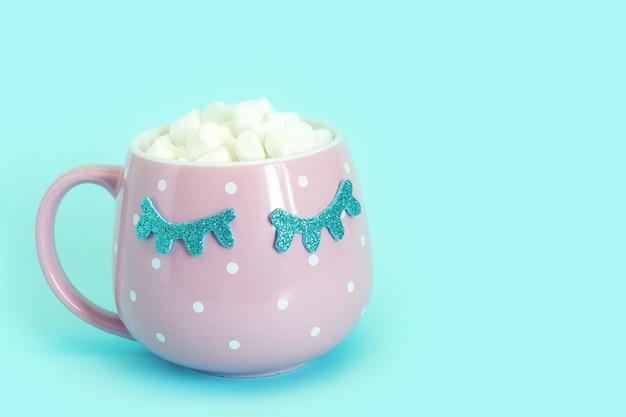 コーヒーとマシュマロで目を閉じた青い水玉模様のピンクのマグカップ。光沢のあるまつげ。青色の背景。 Premium写真