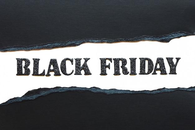 Надпись черная пятница черными блестящими буквами на белом фоне и рваной черной бумаги. Premium Фотографии