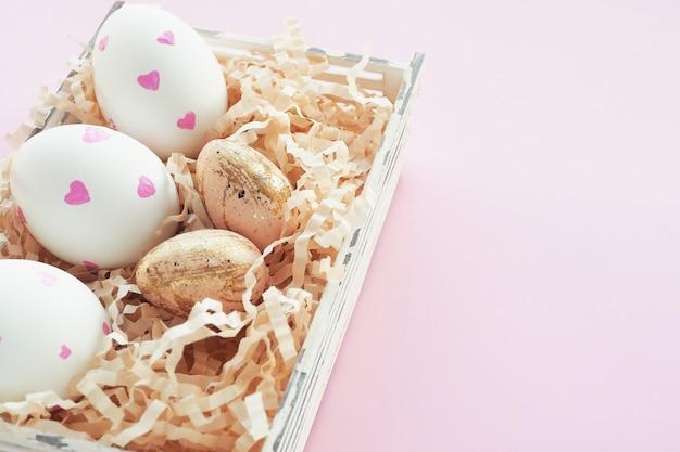 Пасхальные белые яйца с розовыми сердечками и бежевый в черное пятнышко и золотые штрихи в корзине на розовом фоне. Premium Фотографии