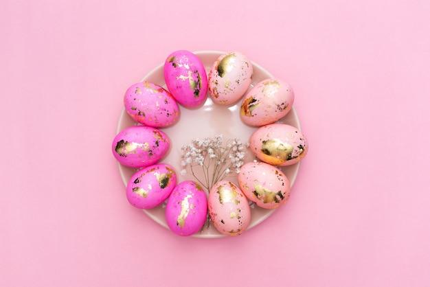 イースター黄金のフレームは、パステル調のピンクの背景に卵を装飾されています。 Premium写真