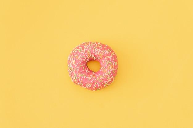 ピンクの背景に落ちる動きで様々な装飾ドーナツ。甘くてカラフルなドーナツが落下したり、飛んでいます。 Premium写真