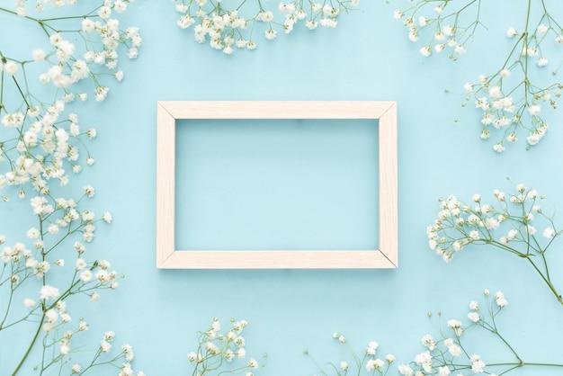 ロマンチックな花の組成。白い石膏の花、パステル調の青い背景上のフォトフレーム。 Premium写真