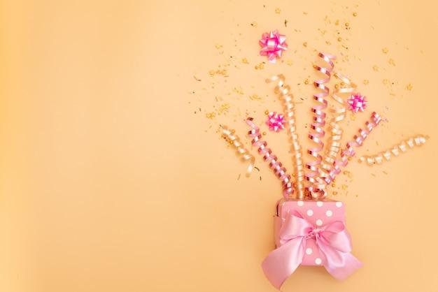 Желтая подарочная коробка с различными партийными конфетти, растяжками, шумоглушителями и украшениями на оранжевом фоне Premium Фотографии