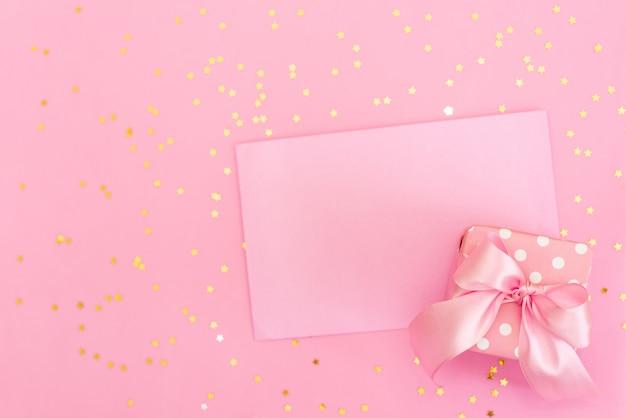 ピンクの背景の封筒にピンクのかぎ針編みの心。バレンタインデーのロマンチックなお祝い。 Premium写真