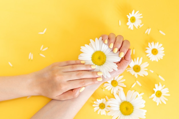 スタイリッシュでお洒落な女性のマニキュア。黄色の背景に美しい若い女性の手。 Premium写真