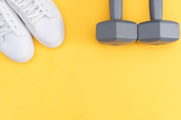 黄色の背景にフィットネスアクセサリー。スニーカー、ボトル入り飲料水、イヤホン、ダンベル。 Premium写真