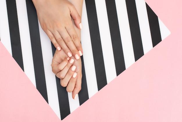 スタイリッシュなトレンディな女性のマニキュア。ピンクの若い女性の手 Premium写真
