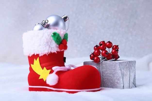 メリークリスマス組成。雪と雪の大波の羽のギフトボックスとサンタの靴。幸せな休日。 Premium写真