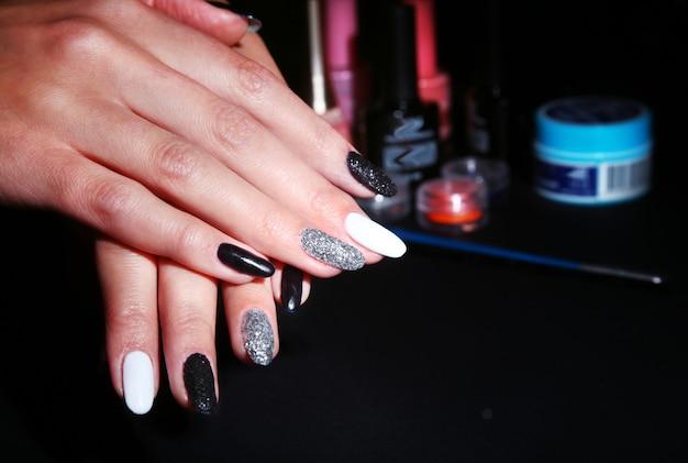 黒、白のネイルアートマニキュア。キラキラと休日スタイル明るいマニキュア。美しさの手。スタイリッシュネイル、マニキュア Premium写真