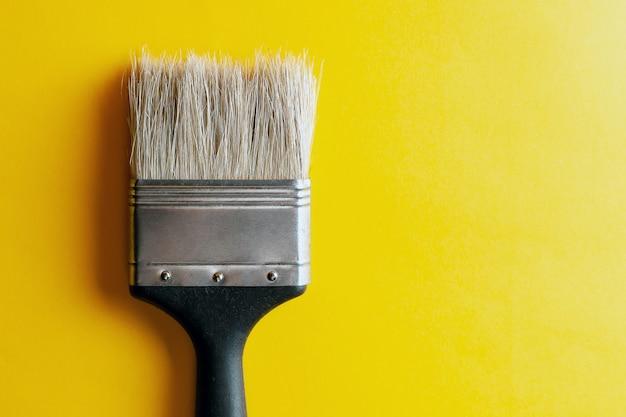 黄色の背景にペイントブラシ。創造的なコンセプトです。デザインや装飾用 Premium写真